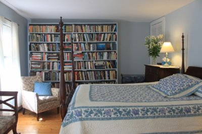 four postered bed in room with wall of books and videos