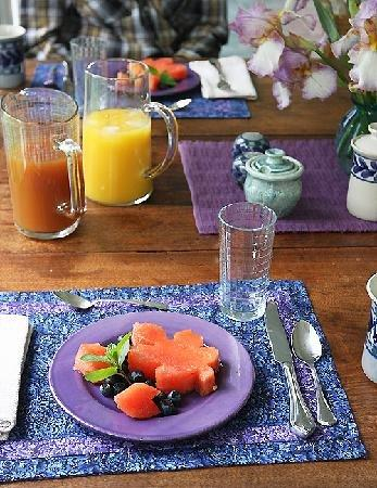 dining table set with fruit course and juices