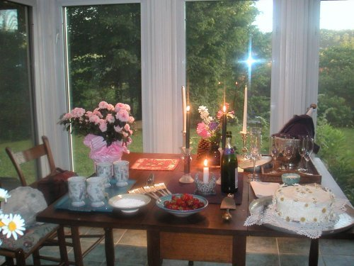 sunroom with table set with flowers, strawberries, cake, candles, champaign bucket
